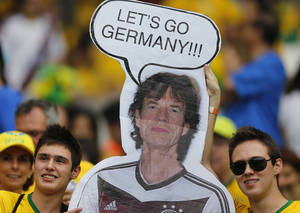 Photo - Brazil supporters hold a poster depicting Rolling Stones singer Mick Jagger wearing a Germany shirt prior to the World Cup semifinal soccer match between Brazil and Germany at the Mineirao Stadium in Belo Horizonte, Brazil, Tuesday, July 8, 2014. (AP Photo/Frank Augstein)