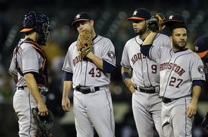 Photo - Houston Astros' Brad Peacock (43) is visited on the mound by teammates prior to being removed in the eighth inning of their baseball game against the Oakland Athletics on Thursday, Sept. 5, 2013, in Oakland, Calif. (AP Photo/Ben Margot)