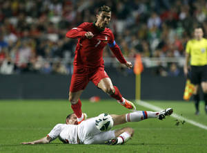 Photo - FILE - In this June 7, 2013, file photo, Portugal's Cristiano Ronaldo gets the ball past Russia's Alexei Kozlov, on the ground, during their 2014 World Cup qualifying group F soccer match, at the Luz stadium in Lisbon. (AP Photo/Armando Franca) - SEE FURTHER WORLD CUP CONTENT AT APIMAGES.COM