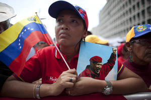 "Photo - A woman holds a picture of Venezuela's President Hugo Chavez and the country's national flag during an event commemorating the violent street protests of 1989 known as the ""Caracazo,""  in Caracas, Venezuela, Wednesday, Feb. 27, 2013. The wave of the 1989 violent protests, seen by the Chavez government as a ""popular uprising,"" was in response to the economic measures imposed by then President Carlos Andres Perez.  (AP Photo/Ariana Cubillos)"