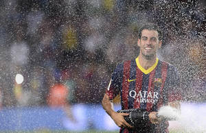 Photo - FC Barcelona's Sergio Busquets sprays champagne after his team victory against Atletico Madrid after a Spanish Supercup at the Camp Nou stadium in Barcelona, Spain, Wednesday, Aug. 28, 2013. Barcelona won the Spanish Super Cup on Wednesday. (AP Photo/Manu Fernandez)