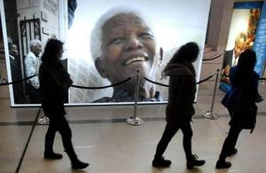Photo - People pass photos of former president Nelson Mandela at the Nelson Mandela Legacy Exhibition in Cape Town, South Africa, Tuesday, July 2, 2013. Mandela remains in critical condition in a Pretoria clinic . (AP Photo/Masixole Feni)