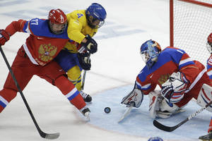 Photo - Inna Dyubanok of Russia (77) ties to keep Jenni Asserholt (4) of Sweden away from Goalkeeper Anna Prugova of Russia (1) during the 2014 Winter Olympics women's ice hockey game at Shayba Arena, Thursday, Feb. 13, 2014, in Sochi, Russia. (AP Photo/Matt Slocum)