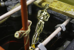 Photo - FILE - In this Jan. 26, 2009 file photo, an Oscar statue is pulled from the final plating process that coats the statue with 24-karat gold at R.S. Owens & Co., in Chicago. The company said it will be laying off 95 workers on Dec. 17, 2012. The cuts come a month after the company announced it was being purchased on Dec. 17 by St. Regis Crystal Inc. of Indianapolis. They have about 250 employees. A news release on the sale said the company will continue to make Oscar and Emmy statues in Chicago.  They have been making the Oscar statues for about 30 years. (AP Photo/M. Spencer Green, File)