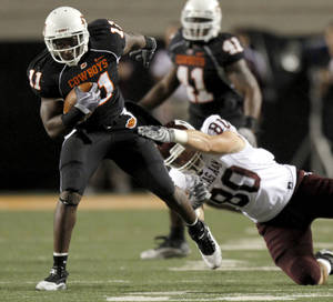 Photo - OSU's Shaun Lewis (11) returns an interception as A&M's Hutson Prioleau (80) tackles him late in the fourth quarter during the college football game between Texas A&M University (TAMU) and Oklahoma State University (OSU) at Boone Pickens Stadium in Stillwater, Okla., Thursday, Sept. 30, 2010. Photo by Sarah Phipps, The Oklahoman