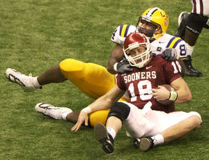 Photo - OU, LSU, COLLEGE FOOTBALL: Louisiana State University's defensive end Marcus Spears (84) takes down the University of Oklahoma's quarterback Jason White (18) during the second half of the Sugar Bowl in New Orleans Sunday, Jan. 4, 2004. (AP Photo/Andrew Cohoon)