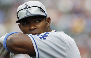 Photo - Los Angeles Dodgers right fielder Yasiel Puig hangs over the dugout rail in the first inning of a baseball game against the Colorado Rockies in Denver, Thursday, July 4, 2013. (AP Photo/David Zalubowski) ORG XMIT: CODZ106