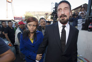 photo - Software company founder John McAfee, right, accompanied by his girlfriend &quot;Sam,&quot; leaves after a press conference outside the Supreme Court in Guatemala City, Tuesday, Dec. 4, 2012. McAfee, 67, who has been identified as a &quot;person of interest&quot; in the killing of his neighbor in Belize, 52-year-old Gregory Faull, has surfaced in public for the first time in weeks, saying Tuesday that he plans to ask for asylum in Guatemala because he fears persecution in Belize. (AP Photo/Moises Castillo)