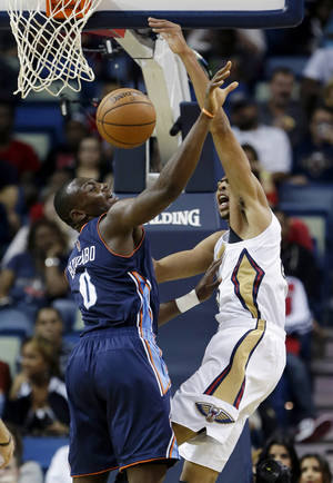 Photo - New Orleans Pelicans forward Anthony Davis, right, vies for a loose ball against Charlotte Bobcats forward Bismack Biyombo (0) in the first half of an NBA basketball game in New Orleans, Saturday, Nov. 2, 2013. (AP Photo/Gerald Herbert)
