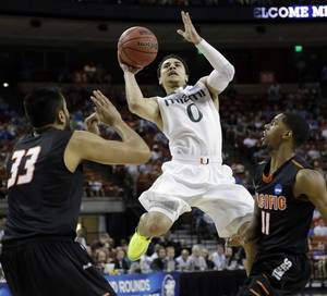 Photo - FILE - In this March 22, 2013 file photo, Miami's Shane Larkin (0) shoots between Pacific's Tony Gill (33) and Lorenzo McCloud (11) during the first half of a second-round game of the NCAA college basketball tournament in Austin, Texas. Larkin is a possible first-round pick in the NBA Draft on June 27. (AP Photo/David J. Phillip)