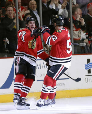 Photo - Chicago Blackhawks center Andrew Shaw (65) celebrates his goal with Brandon Bollig (52) during the first period of an NHL hockey game against the Columbus Blue Jackets on Thursday, March 6, 2014, in Chicago. (AP Photo/Charles Rex Arbogast)
