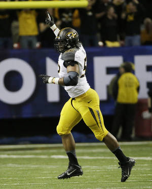 Photo - Missouri defensive lineman Michael Sam (52) reacts after Auburn fumbled and Missouri recovered during the first half of the Southeastern Conference NCAA football championship game, Saturday, Dec. 7, 2013, in Atlanta. (AP Photo/David Goldman)
