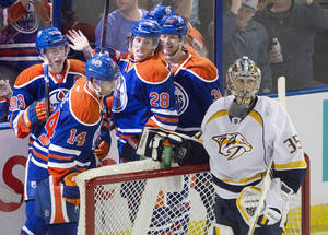 Photo - Nashville Predators goalie Pekka Rinne (35) looks on as Edmonton Oilers' Ryan Nugent-Hopkins (93), Jordan Eberle (14), Ryan Jones (28) and Philip Larsen (36) during the second period of an NHL hockey game Tuesday, March 18, 2014, in Edmonton, Alberta. (AP Photo/The Canadian Press, Jason Franson)