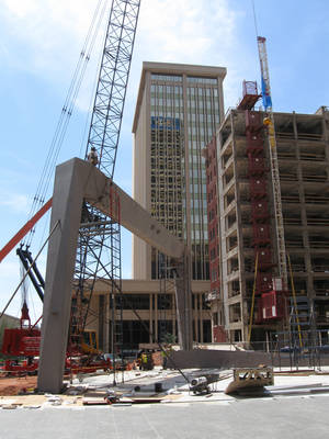 Photo - A large modern archway, part of a planned canopy at SandRidge Commons, is erected as renovations of the adjoining Braniff Building continue. <strong>Steve Lackmeyer</strong>