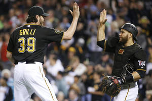 Photo - Pittsburgh Pirates closer Jason Grilli (39)  celebrates with catcher Russell Martin after getting the save in a 4-3 Pirates win over the Washington Nationals in a baseball game in Pittsburgh, Friday, May 23, 2014. (AP Photo/Gene J. Puskar)