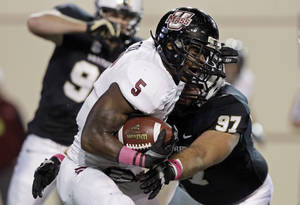 Photo -   Massachusetts running back Michael Cox (5) is tackled by Vanderbilt defensive tackle Jared Morse (97) during the first quarter of an NCAA college football game Saturday, Oct. 27, 2012, in Nashville, Tenn. (AP Photo/Wade Payne)