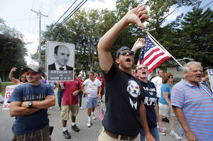 Photo - Market Basket employees and supporters jeer at a car driving into the supermarket's headquarters in Tewksbury, Mass., Monday, Aug. 18, 2014. As an employee revolt at the New England grocery store chain headed into its fifth week, the governors of Massachusetts and New Hampshire made the unusual move of personally stepping into negotiations aimed at ending a standoff threatening the future of the popular low-priced supermarkets. (AP Photo/Elise Amendola)
