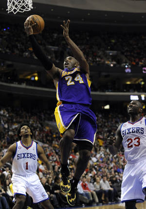 Photo - Los Angeles Lakers' Kobe Bryant (24) shoots over Philadelphia 76ers' Jason Richardson (23) and Nick Young (1) during the first half of an NBA basketball game on Sunday, Dec. 16, 2012, in Philadelphia. (AP Photo/Michael Perez)