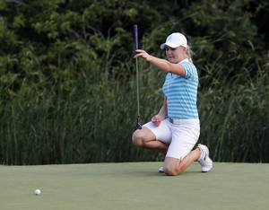 Photo - Europe's Charley Hull, of England, lines up a birdie putt on the 17th hole during four-ball matches at the Solheim Cup golf tournament Saturday, Aug. 17, 2013, in Parker, Colo. Hull made the putt. (AP Photo/Ed Andrieski)