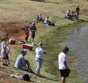 Photo - Children and their parents line the banks during a fishing derby at Little River Park in Moore.  Photos by Paul Hellstern, The Oklahoman