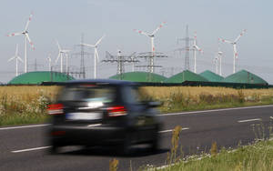 Photo - FILE - In this June 29, 2011 file photo a car passes by a biogas plant and windmills near Nauen, Germany. Chancellor Angela Merkel vowed to defend German jobs as the European Union's executive launched an investigation Wednesday, Dec. 18, 2013, into whether German companies that use large amounts of electricity get unfair discounts. Hundreds of German companies have been largely exempt from a surcharge on electricity bills used to promote renewable energy sources such as solar and wind, which other consumers pay. (AP Photo/Ferdinand Ostrop)
