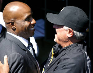 Photo - Former Pittsburgh Pirates outfielder Barry Bonds, left is greeted by current manager Clint Hurdle during opening day ceremonies before the baseball game between the Pittsburgh Pirates and the Chicago Cubs on Monday, March 31, 2014, in Pittsburgh.  (AP Photo/Keith Srakocic)