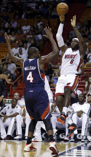 Photo - Miami Heat's LeBron James (6) prepares to pass as Atlanta Hawks' Paul Millsap (4) defends in the first quarter of an NBA preseason basketball game, Monday, Oct. 7, 2013, in Miami. (AP Photo/Alan Diaz)