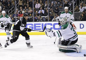 Photo - Dallas Stars goalie Kari Lehtonen, right, of Finland, makes a save off a shot by Los Angeles Kings' Justin Williams, left, during the second period of an NHL hockey game on Monday, Dec. 23, 2013, in Los Angeles. (AP Photo/Jae C. Hong)