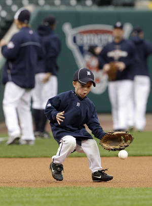photo -   Gage Brookens, grandson of Detroit Tigers first base coach Tom Brookens, goes after a ground ball during a baseball workout at Comerica Park in Detroit, Friday, Oct. 26, 2012. The Tigers host the San Francisco Giants in Game 3 of baseball's World Series on Saturday. The Giants lead the best-of-seven games series 2-0. (AP Photo/Patrick Semansky)