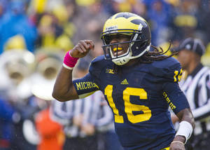 "Photo -   Michigan quarterback Denard Robinson celebrates his touchdown with an ""eating"" gesture in the second quarter of an NCAA college football game against Illinois, Saturday, Oct. 13, 2012, in Ann Arbor, Mich. (AP Photo/Tony Ding)"