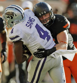Photo - Oklahoma State's Caleb Lavey (45) tackles Kansas State's Daniel Sams (4) during a college football game between the Oklahoma State University Cowboys (OSU) and the Kansas State University Wildcats (KSU) at Boone Pickens Stadium in Stillwater, Okla., Saturday, Oct. 5, 2013. OSU won, 33-29. Photo by Nate Billings, The Oklahoman