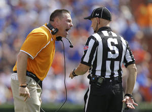 Photo - Tennessee head coach Butch Jones, left, has word with side judge Chris Conley during the first half of an NCAA college football game against Florida in Gainesville, Fla., Saturday, Sept. 21, 2013.(AP Photo/John Raoux)