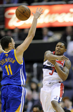 photo - Washington Wizards guard Bradley Beal (3) passes the ball past Golden State Warriors guard Klay Thompson (11) during the first half of an NBA basketball game, Saturday, Dec. 8, 2012, in Washington. (AP Photo/Nick Wass)