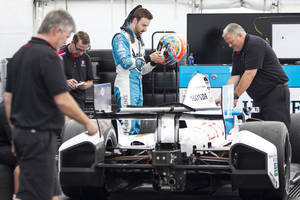 Photo - Canadian driver James Hinchcliffe steps into his car as his team prepares to weigh it Thursday, July 17, 2014, ahead of this weekend's IndyCar auto races. (AP Photo/The Canadian Press, Chris Young)