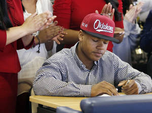 Photo - NATIONAL SIGNING DAY / SIGN / SIGNED: Heritage Hall's Sterling Shepard signs to play football for the University of Oklahoma (OU) as family members applaud during the National Signing Day ceremony at Heritage Hall in Oklahoma City, Wednesday, Feb. 1, 2012. Photo by Nate Billings, The Oklahoman