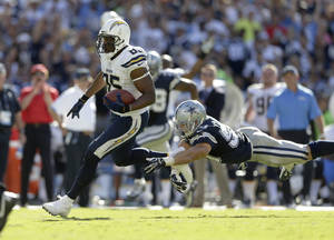 Photo - San Diego Chargers tight end Antonio Gates, left, scores past Dallas Cowboys middle linebacker Sean Lee during the second half of an NFL football game Sunday, Sept. 29, 2013, in San Diego. (AP Photo/Gregory Bull)