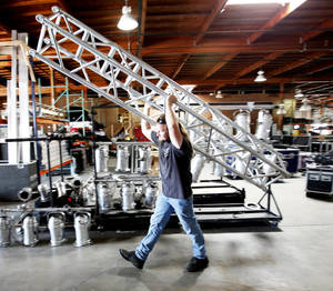 Photo - Chris Moad carries a truss used for stage and concert lighting at Toucan Lighting in Oklahoma City.