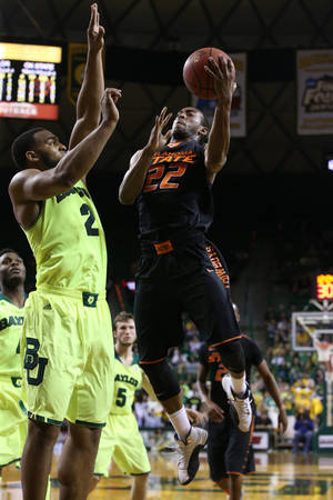 Photo - Oklahoma State guard Markel Brown (22) shoots over Baylor forward Rico Gathers (2), left, in the first half of an NCAA college basketball game, Monday, Feb. 17, 2014, in Waco, Texas. (AP Photo/Waco Tribune Herald, Rod Aydelotte)