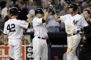 Photo -   New York Yankees' Brett Gardner, left, and Russell Martin, center, greet Derek Jeter at the plate after Jeter's fourth-inning, three-run home run against the Los Angeles Angels during their baseball game at Yankee Stadium in New York, Sunday, April 15, 2012. (AP Photo/Kathy Willens)