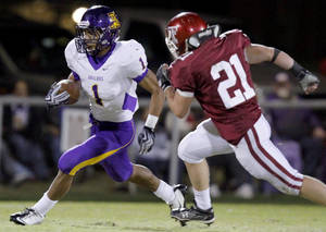 Photo - Anadarko's Sheldon Wilson gets by Tuttle's Toby Coats during the high school football game between Tuttle and Anadarko, Friday, Oct. 29, 2010, in Tuttle, Okla. Photo by Sarah Phipps, The Oklahoman