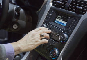 photo - An industry affiliate tests out Ford's SYNC connection and entertainment system inside a Ford Fusion at the Consumer Electronics Show, Wednesday, Jan. 9, 2013, in Las Vegas. Ford's SYNC connects the car stereo and navigation system to a user's mobile device. (AP Photo/Julie Jacobson)