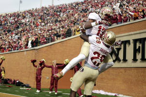 Photo - Florida State defensive back Jalen Ramsey, top, jumps into the arms of teammate Nate Andrews after Andrews ran back an interception for a touchdown against Wake Forest in the first half of an NCAA college football game in Winston-Salem, N.C., Saturday, Nov. 9, 2013. (AP Photo/Nell Redmond)