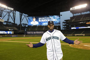 Photo - Robinson Cano poses for a photo in his new jersey at Safeco Field after he was introduced as the newest member of the Seattle Mariners baseball team, Thursday, Dec. 12, 2013, in Seattle. (AP Photo/Ted S. Warren)