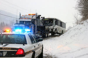 Photo - A bus is towed after the driver lost control and struck an embankment on Route 220 in Cumberland Valley Twp., Pa., Sunday, Feb. 9, 2014, according to the police. More than 20 passengers were injured in the crash. (AP Photo/Bedford Gazette, Bridgett Weaver)