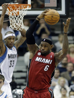 Photo - Miami Heat's LeBron James, right, beats Minnesota Timberwolves' Dante Cunningham in the second half of an NBA basketball game for one of his 10 rebounds Monday, March 4, 2013, in Minneapolis. The Heat won 97-81. (AP Photo/Jim Mone)