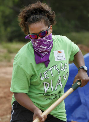 Photo - Courtney Gray shovels mulch into a wheel barrow. Organizers said about 140 volunteers from Partners in Public Health, Blue Cross and Blue Shield of Oklahoma, organizers from KaBOOM! and residents of the Oklahoma City community will provided the labor on Saturday, June 8, 2013, to build a new playground at the Northeast Regional Health and Wellness Center on NE 63 Street, east of MLK Blvd.  The new playground's design is based on drawings created by children who participated in a Design Day event in April.   Photo  by Jim Beckel, The Oklahoman.