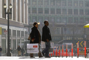 Photo - FILE - In this Tuesday, Dec. 24, 2013, file photo, a man and woman carry shopping bags as they cross the street in San Francisco..The Commerce Department releases retail sales data for December on Tuesday, Jan. 14, 2014. (AP Photo/Jeff Chiu)