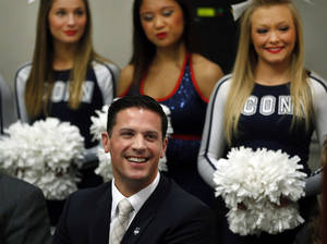 Photo - Cheerleaders stand behind Bob Diaco, former Notre Dame defensive coordinator, as he is introduced as Connecticut's new head football coach during a news conference on campus in Storrs, Conn., Thursday, Dec. 12, 2013. (AP Photo/Elise Amendola)