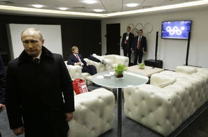 Photo - In this first in a sequence of four images, Russian President Vladimir Putin waits in the presidential lounge to be introduced at the opening ceremony of the 2014 Winter Olympics on Friday, Feb. 7, 2014, in Sochi, Russia. Behind him, a TV screen shows four of the Olympic rings opening at the start of the ceremony, while the fifth ring remains closed. (AP Photo/David Goldman, Pool)