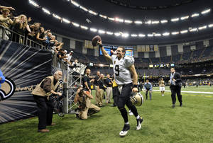 Photo - New Orleans Saints quarterback Drew Brees (9) responds to the crowd as he walks off the field after an NFL football game against the Miami Dolphins in New Orleans, Monday, Sept. 30, 2013. The Saints won 38-17. (AP Photo/Bill Feig)
